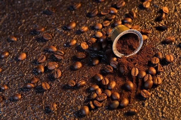 Espressokaffeekapseln auf holzoberfläche mit einigen röstkaffeebohnen