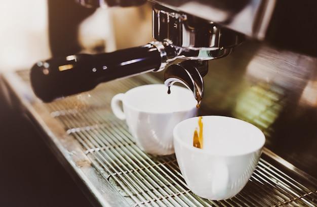 Espressomaschine, die einen kaffee braut. kaffee, der in gläser in der kaffeestube, espresso gießt aus kaffeemaschine gießt
