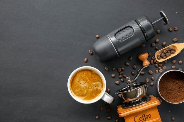 Espressomaschine, tasse und bohne auf schwarzem holztisch. draufsicht