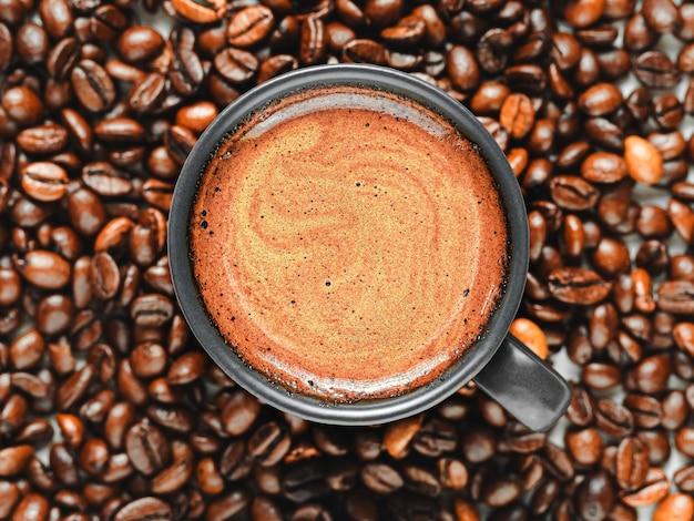 Espressotasse mit schaum zwischen gerösteten kaffeebohnen