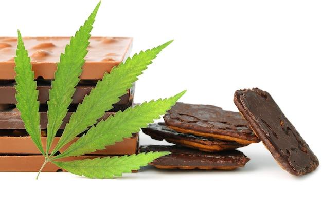 Essbare medizinische marihuana-lebensmittelschokoladenriegel und schokoladenplätzchen mit grünem hanfblatt isoliert