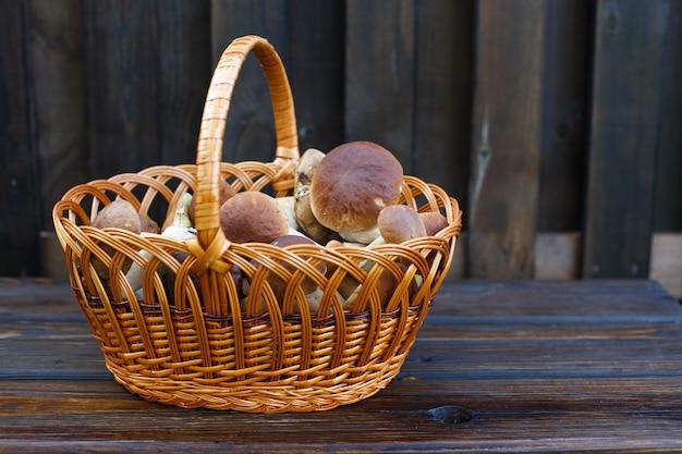 Essbare pilze steinpilze im weidenkorb auf dem hölzernen hintergrund
