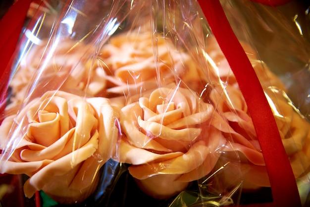 Essbare rosen eines blumenstraußes der weißen schokolade in der geschenkverpackungsnahaufnahme.
