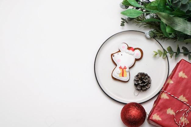 Essbares rattenmäusekeks auf einer tabelle mit weihnachtsbaumdekorationen