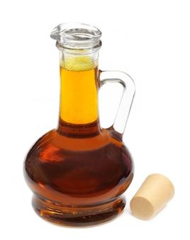 Essbares senföl in einer transparenten flasche auf weißem hintergrund