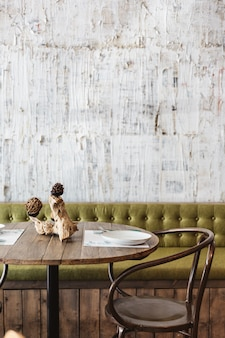 Essbereich mit grünem sofa, holztisch, schwarzem stahlstuhl und weißer kratzerbeschaffenheitstapete. modernes interieur restaurant atmosphäre.