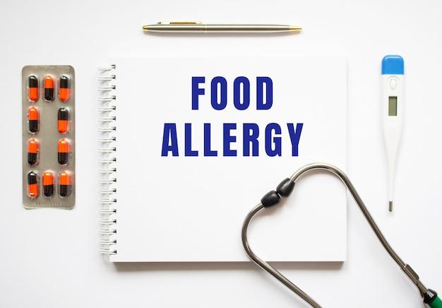 Essen allergie text geschrieben in einem notizbuch, das auf einem schreibtisch und einem stethoskop liegt