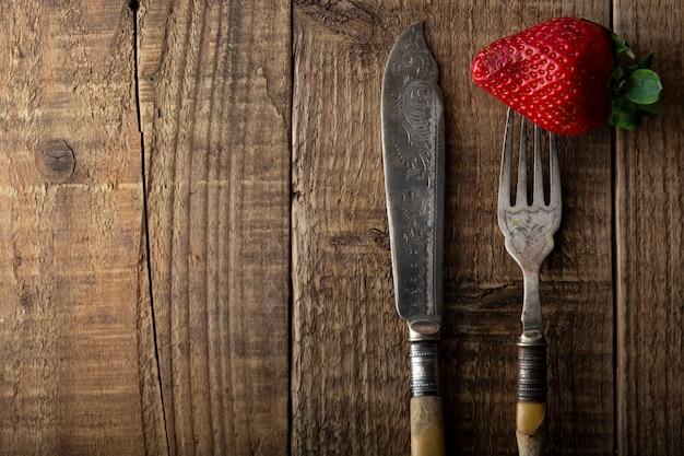 Essen frische erdbeeren, vintage besteck gabel und messer. strukturierter, rustikaler holztisch.