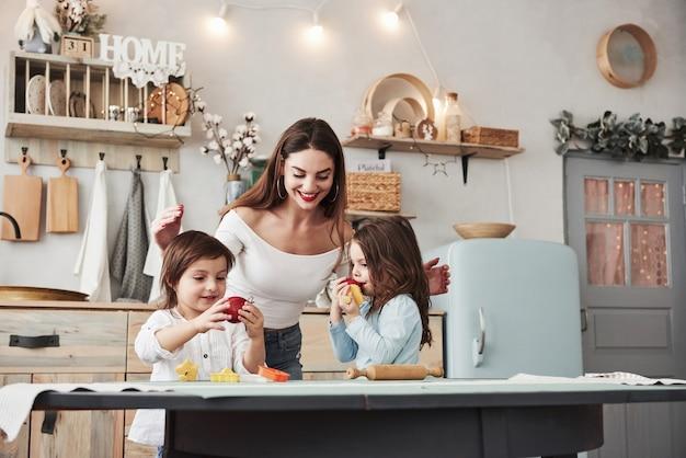 Essen frisches obst. junge schöne frau füttert zwei kinder mit äpfeln, während sie mit spielzeug am tisch sitzen.
