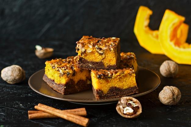 Essen für halloween. selbst gemachter schokoladenschokoladenkuchen mit nüssen und einer schicht kürbis. zimt