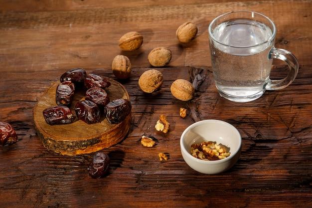 Essen für iftar im heiligen ramadan auf einem holztisch datteln, nüsse und wasser. horizontales foto
