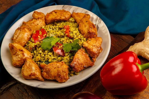 Essen für suhoor im ramadan bulgur schnell mit rindfleisch in einem teller auf einer blauen serviette. horizontales foto