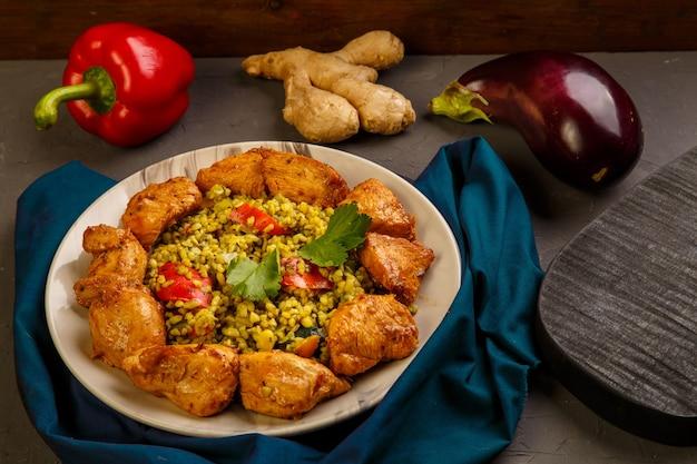 Essen für suhoor im ramadan bulgur schnell mit rindfleisch in einem teller auf einer blauen serviette neben gemüse. horizontales foto