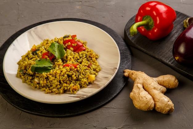 Essen für suhoor im ramadan-bulgurpfosten mit gemüse in einem teller auf grauem hintergrund nahe gemüse auf einem brett. horizontales foto