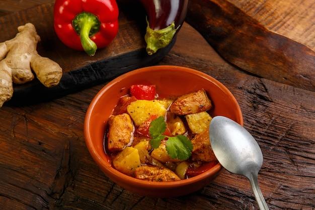 Essen für suhoor im ramadan-lammeintopf mit kartoffelgemüse und einem löffel auf einem hölzernen hintergrund.