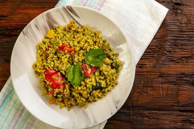 Essen für suhoor in ramadan bulgur post mit gemüse in einem teller auf einem holztisch auf einer serviette. horizontales foto