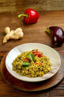 Essen für suhoor in ramadan bulgur post mit gemüse in einem teller auf einem holztisch neben gemüse auf einem brett. vertikales foto