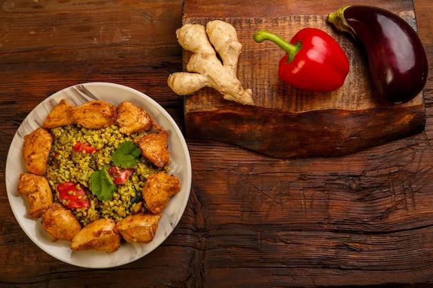 Essen für suhoor in ramadan bulgur post mit rindfleisch in einem teller auf einem holztisch. horizontales foto