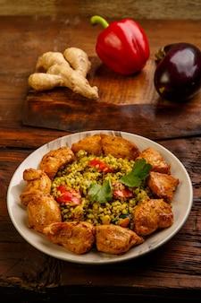 Essen für suhoor in ramadan bulgur post mit rindfleisch in einem teller auf einem holztisch neben gemüse auf einem brett. vertikales foto