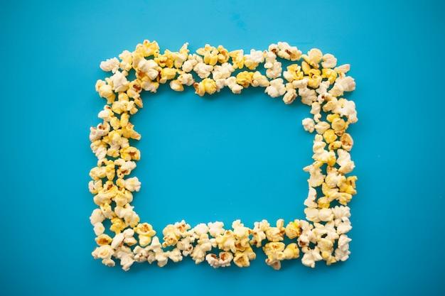 Essen. gefrorenes popcorn-mais-köstliches gelbes popcorn auf blau. kino. exemplar. platz für text