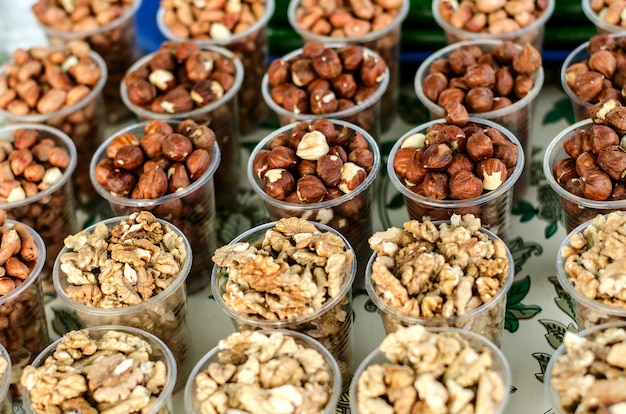 Essen hintergrund. verschiedene nüsse in plastikbechern.