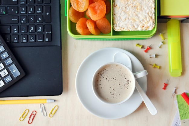 Essen im büro oder in der schule. brotdose mit gesundem essen und einer tasse kaffee auf dem desktop. draufsicht
