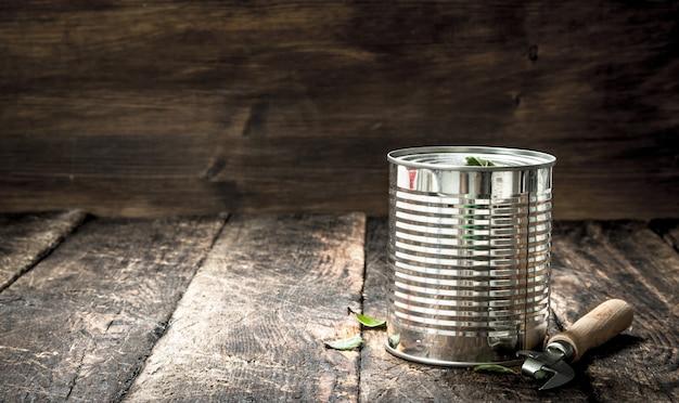 Essen in blechdose mit öffner. auf einem hölzernen hintergrund.