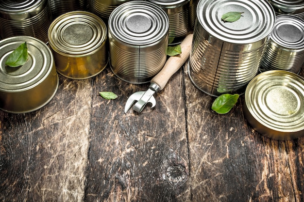 Essen in blechdosen mit öffner. auf einem hölzernen hintergrund.
