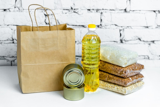 Essen in einer papiertüte für spenden, auf einem weißen backsteinhintergrund. anti-krisen-bestand an wesentlichen gütern für die zeit der quarantäneisolation. lebensmittellieferung, coronavirus.