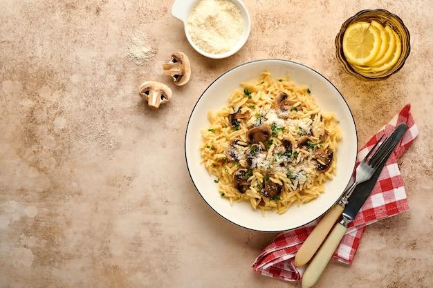 Essen italienische pasta risoni, champignons, sauce, parmesan, thymian, knoblauch, olivenöl, in weißem teller