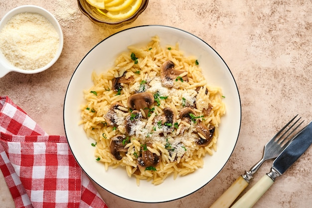 Essen italienische pasta risoni, champignons, sauce, parmesan, thymian, knoblauch, olivenöl, in weißer platte über schiefer