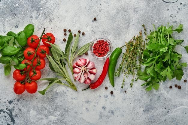 Essen kochen hintergrund. frischer safran, knoblauch, koriander, basilikum, kirschtomaten, paprika und olivenöl, gewürzkräuter und gemüse am hellgrauen schiefertisch. draufsicht der lebensmittelzutaten.
