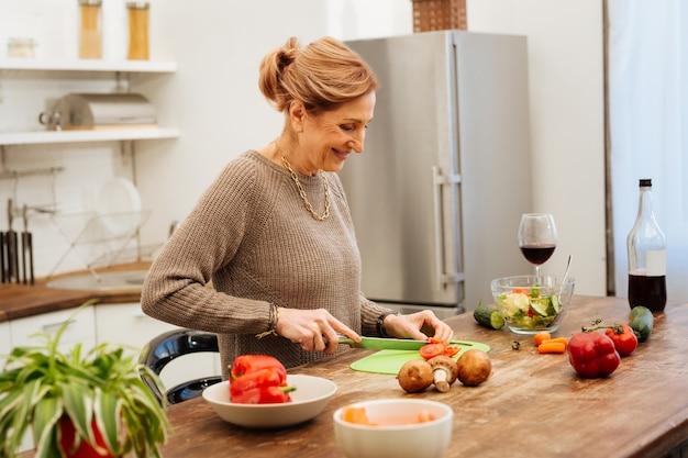 Essen kochen. lächelnde gutaussehende frau mit guter laune beim kochen von leichtem salat