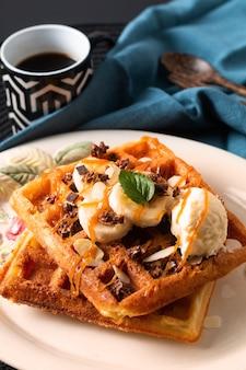 Essen mahlzeit frühstückskonzept hausgemachte bio-waffeln bananen-vanille-eis-topping mit karamellsauce auf schwarzem hintergrund mit kopienraum