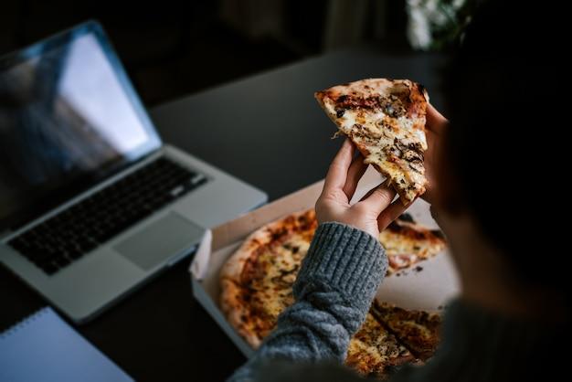 Essen pizza und social networking mit einem laptop.