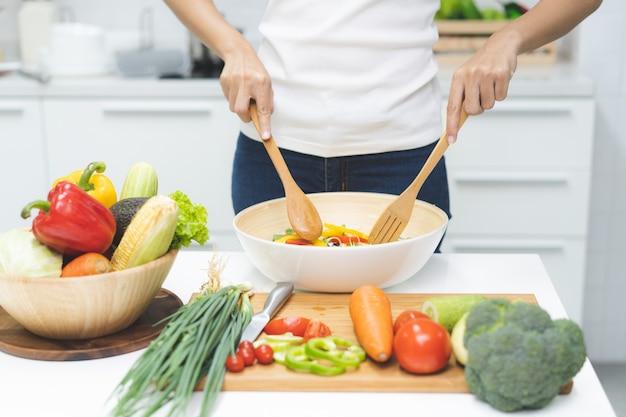 Essen sie gesundes essen für ein gutes wellness-gesundheitskonzept. frau, die salatmenü mit frischem organischem gemüse kocht