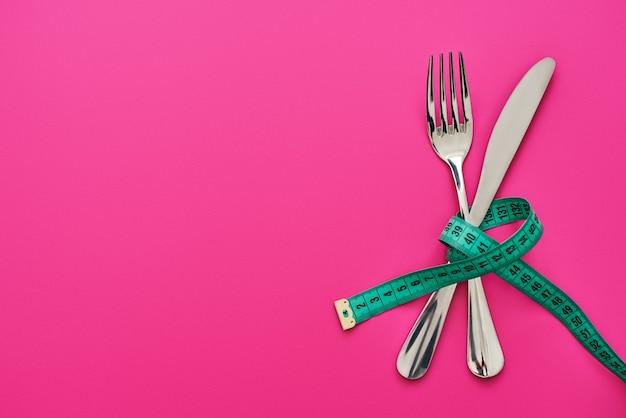 Essen sie nicht zu viel. messer und gabel gekreuzt, verbunden durch maßband einzeln auf rosa hintergrund