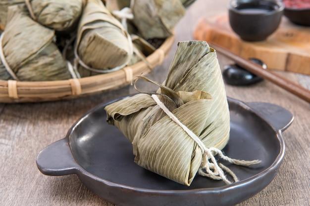 Essen sie zongzi (reisknödel) auf dragon boat festival, asiatisches traditionelles essen