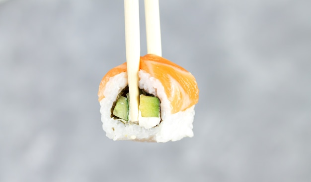 Essen sushi philadelphia roll mit stäbchen nahaufnahme, japanische essen sushi roll im restaurant.