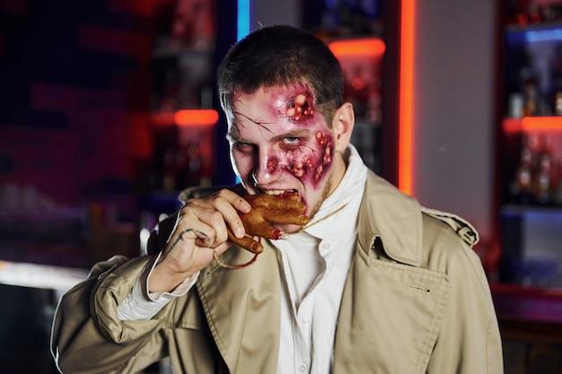 Essen tote hand. porträt des mannes, der auf der thematischen halloween-party in zombie-make-up und -kostüm ist.