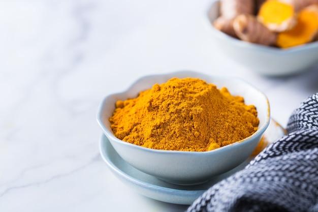 Essen und trinken, diäternährung, gesundheitskonzept. rohe organische orangen-kurkuma-wurzel und -pulver, curcuma longa auf einem kochtisch. indische orientalische cholesterinarme gewürze. raumhintergrund kopieren