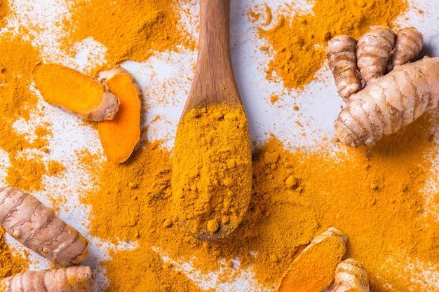 Essen und trinken, diäternährung, gesundheitskonzept. rohe organische orangen-kurkuma-wurzel und -pulver, curcuma longa auf einem kochtisch. indische orientalische cholesterinarme gewürze.