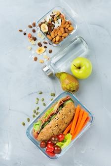 Essen und trinken, stillleben, diät und ernährung, gesunde ernährung, konzept zum mitnehmen. lunchbox mit sandwich, obst, gemüse, nussmischung und einer flasche wasser. draufsicht flach legen hintergrund