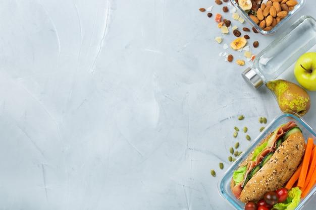 Essen und trinken, stillleben, diät und ernährung, gesunde ernährung, konzept zum mitnehmen. lunchbox mit sandwich, obst, gemüse, nussmischung und einer flasche wasser. draufsicht flach legen, raumhintergrund kopieren