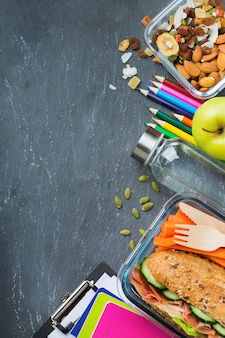Essen und trinken, stillleben, diät und ernährung, gesunde ernährung, konzept zum mitnehmen. schulbrotdose und schreibwaren. draufsicht flach legen, platz tafelhintergrund kopieren
