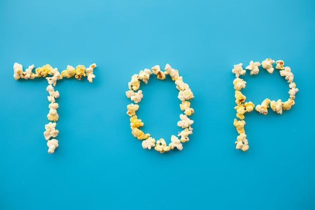 Essen. wort nach oben. popcorn-eimer. köstliches popcorn auf blau. kino.