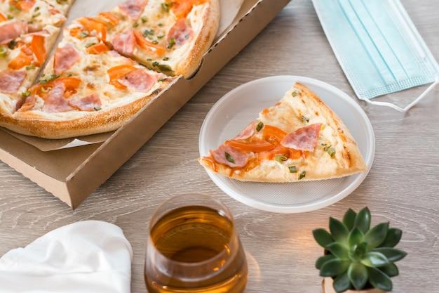 Essen zum mitnehmen. ein stück pizza in einem einweg-plastikteller, eine schutzmaske und eine schachtel pizza auf dem tisch in der küche.