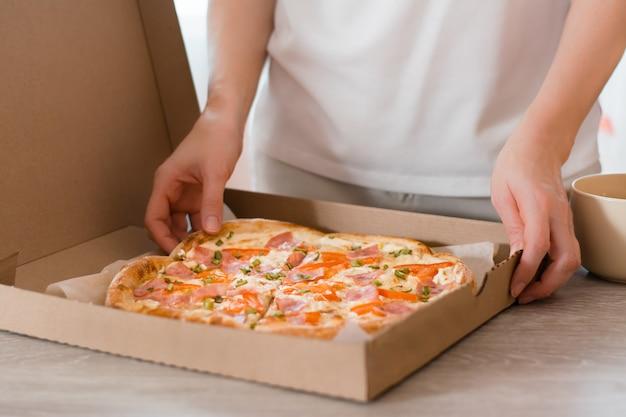 Essen zum mitnehmen. eine frau hält einen karton mit verzehrfertiger pizza auf dem tisch in der küche.