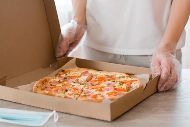 Essen zum mitnehmen. eine frau in einweghandschuhen hält eine pappschachtel pizza und eine schutzmaske auf dem tisch in der küche