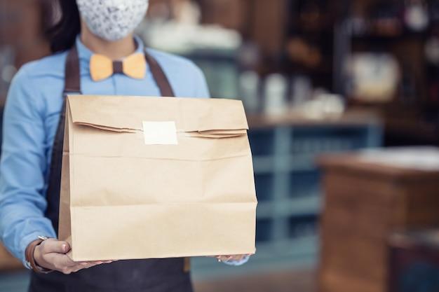 Essen zum mitnehmen in einer papiertüte, die von einer restaurantkellnerin übergeben wird, da der betrieb eingeschränkt ist.